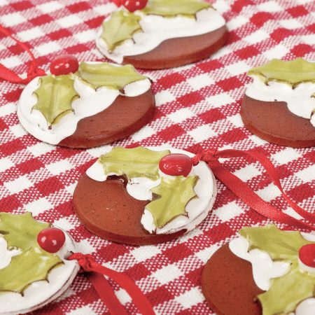 A photo of a selection of Christmas pudding decorations on a checked gingham tablecloth