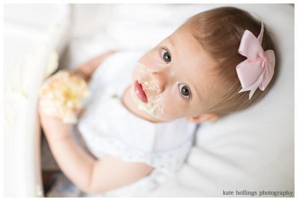 Baby girl looks at camera during cupcake smash