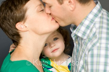 Nashville Photographer- parents kissing while little girl looks at camera