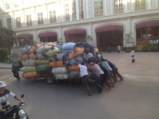 8 men needed to push a ton of denim clothing from the Cambodian to the Thai border crossing.