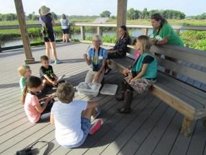 Sarasota Audubon nature center children study feathers with Ann