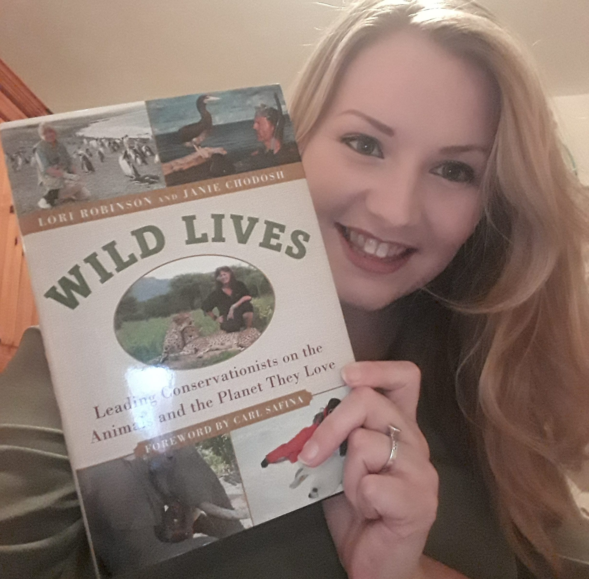 Kate on Conservation holds Wild Lives book by Lori Robinson and Janie Chodosh