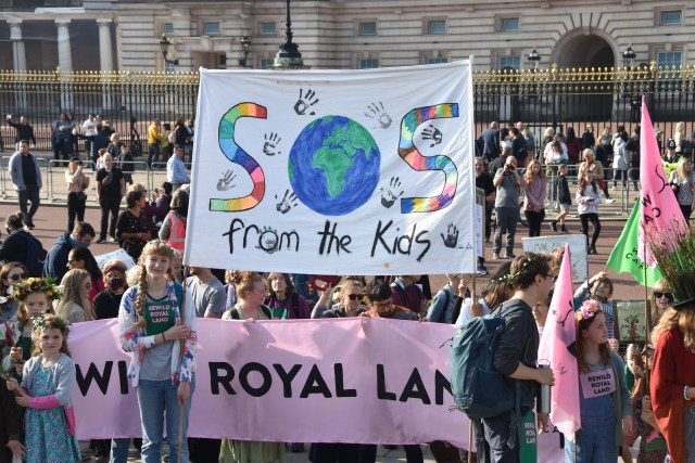 rewild royal land banner and SOS from the kids banner outside Buckingham Palace