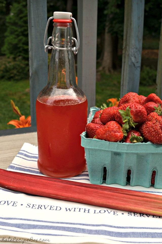A bottle with red liquid sits next to a container of strawberries and stalk of rhubarb.