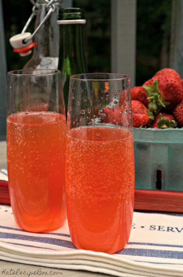 Two stemless wine glasses are filled with a red, bubbly liquid. Strawberries, rhubarb, and bottles are in the background.