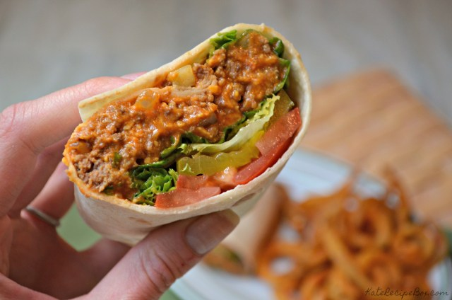 A white hand holds half a flour tortilla filled with cooked ground beef, lettuce, tomatoes, and pickles.