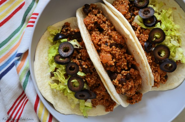 Three flour tortillas in a grey bowl stuffed with a mixture of quinoa and black beans in a seasoned tomato sauce. The outside tortillas are topped with lettuce and black olives. The bowl rests on a napkin with colorful stripes.