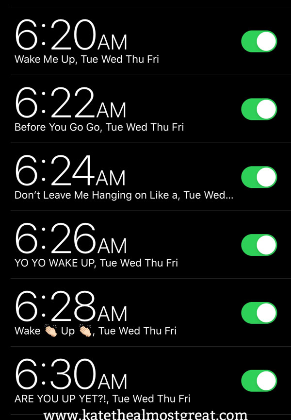 """A screenshot of alarms on Kate's phone. The times from top to bottom are 6:22, 6:24, 6:26, 6:28, and 6:30. The text reads, in order: """"Wake Me Up, Tue Wed Thu Fri"""", """"Before You Go Go, Tue Wed Thu Fri"""", """"Don't Leave Me Hanging on Like a, Tue Wed..."""", """"YO YO WAKE UP, Tue Wed Thu Fri"""" """"Wake Up, Tue Wed Thu Fri"""", and """"ARE YOU UP YET?!, Tue Wed Thu Fri""""."""