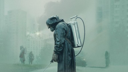 Screen shot from the HBO series Chernobyl showing a man in a hazmat suit spraying water to control radioactive dust