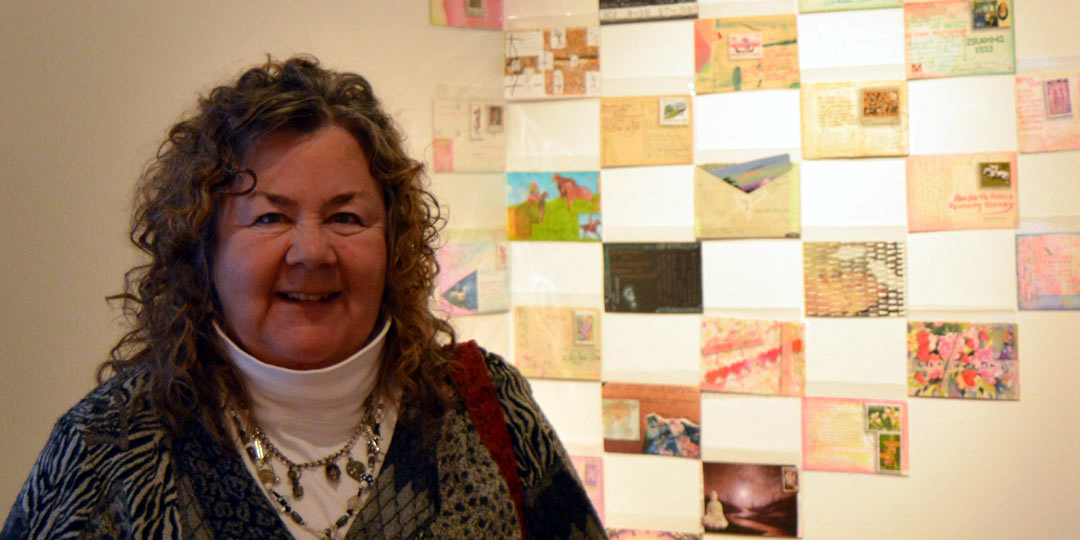 "Kathleen O'Brien with some of the 365 postcards ""Each Day in the Year of the Fire Dog"" at Juxtapose exhibit"