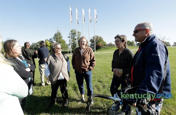 "From left, project organizer Kate Sprengnether, left and artists including Kathleen O'Brien, Janice Durham, Mary Rezny, and Don Ament gathered near flag designed by fellow artist Jim Eichner (back to camera) after a press conference unveiling flags ""Blazing"" the Legacy Trail at Lexmark near the Legacy Trail in Lexington, Ky., on Oct. 13, 2015. Photo by Pablo Alcala 