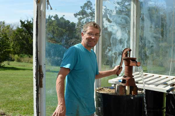 Greg pumping water, greenhouse makeover