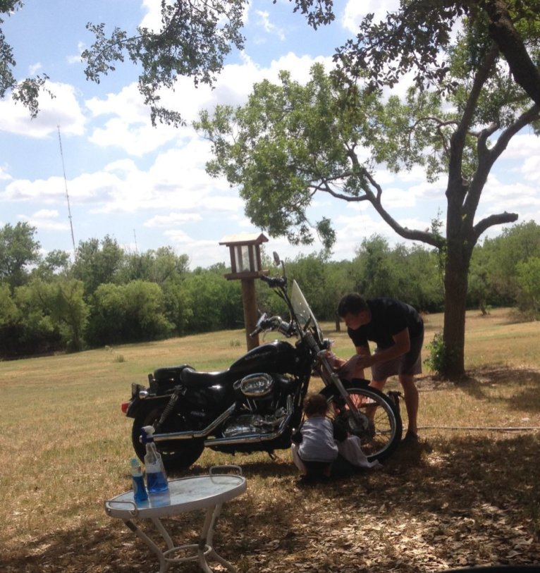 Teaching his nephew how to clean a Harley