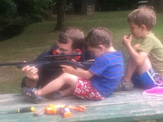 Uncle David, a Marine Rifleman, helped teach Colin and Elijah how to safely handle a BB gun. They shot at gallon jugs filled with water.