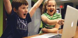 Kids cheering at computer