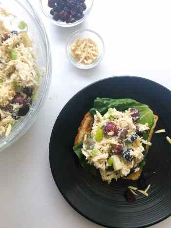 This lightened up chicken salad has amazing texture - crunch from the almonds and celery, chewiness from the craisins, and sweet and juiciness from the apples and grapes. No guilt thanks to substituting greek yogurt for the mayo. Perfect for you weekday lunch prep or your next picnic or potluck. Recipe at KathleensCravings.com #lighterchickensalad #healthyrecipe #picnicrecipes #mealprep #easychickenrecipe