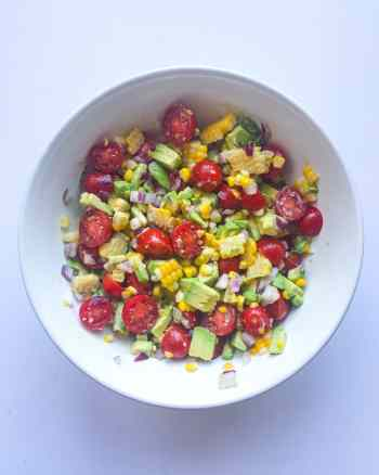Flavorful and easy to toss together. This Corn, Tomato, and Avocado Salad is a perfect use for any leftover corn on the cob you have. Serve cold or room temperature so a great option for potlucks or backyard barbecues. Recipe at Kathleenscravings.com #summersalad #avocadorecipe #cornonthecob #potluckrecipe