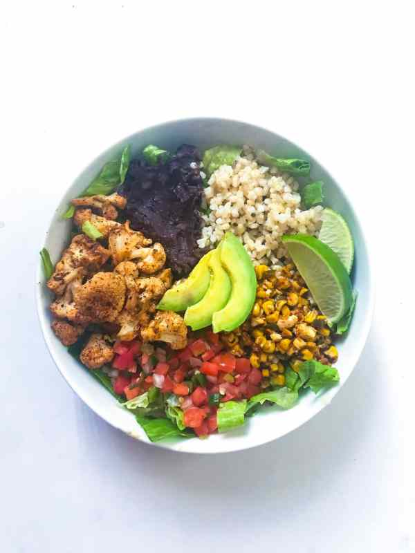 Simple meatless, meal prep meal. Vegan Roasted Cauliflower Burrito Bowl filled with the fix-ins of your choice and brought together with the easy taco roasted cauliflower.
