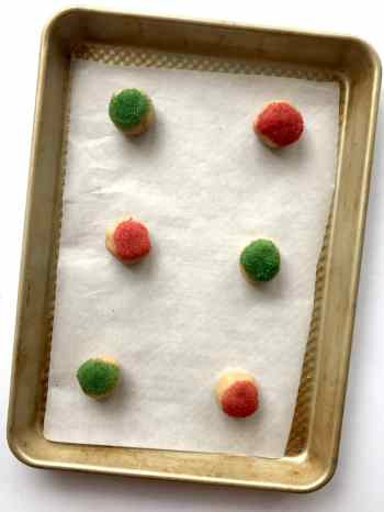 Cookie dough balls with sprinkles on a baking sheet