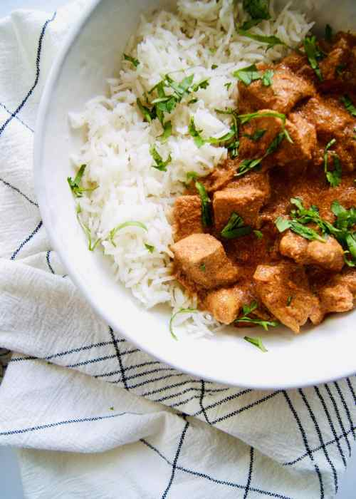 Indian butter chicken with white rice, sprinkled with cilantro in a bowl on top of a dish towel