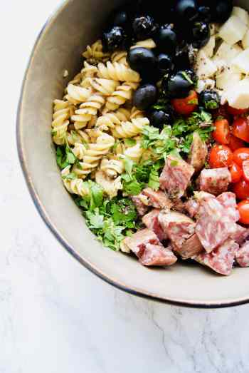 pasta, olive, mozzarella, salami, tomatoes, and parsley in a bowl