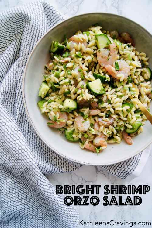 Shrimp orzo salad in a bowl with a gold fork