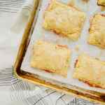 Cinnamon Glazed Peach Pop Tarts are the perfect way to use summer peaches. Made quick by using frozen puff pastry, these pop tarts only take 15 minutes to prep. Topped with an easy cinnamon icing. Recipe at KathleensCravings.com #KathleensCravings #puffpastryrecipe #peachrecipe #poptarts #peachdessert #cinnamonicing