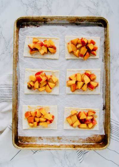 Full-sheet-pan-of-peaches-on-puff-pastry-for-pop-tarts