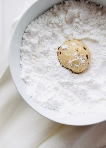 snowball cookies in bowl of powdered sugar