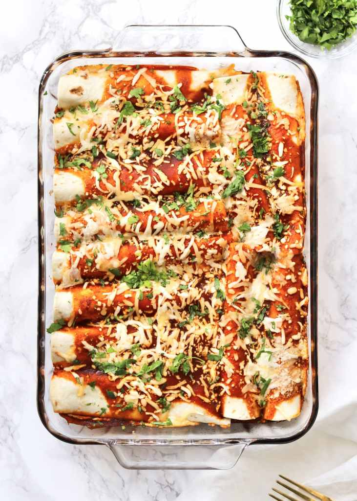 Baked cheesy black bean enchiladas with cilantro and a fork