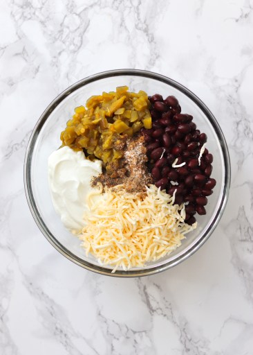 Black beans, green chiles, Greek yogurt, shredded cheese and spices in bowl