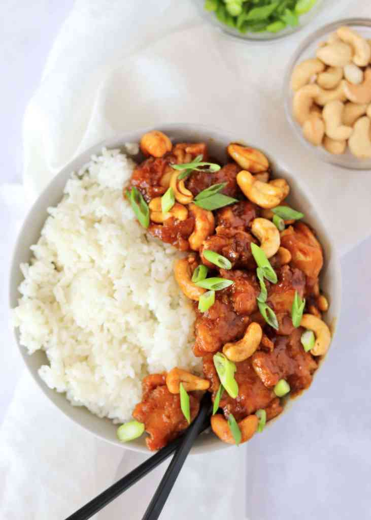 30 minute cashew chicken with white rice in a bowl with chopsticks