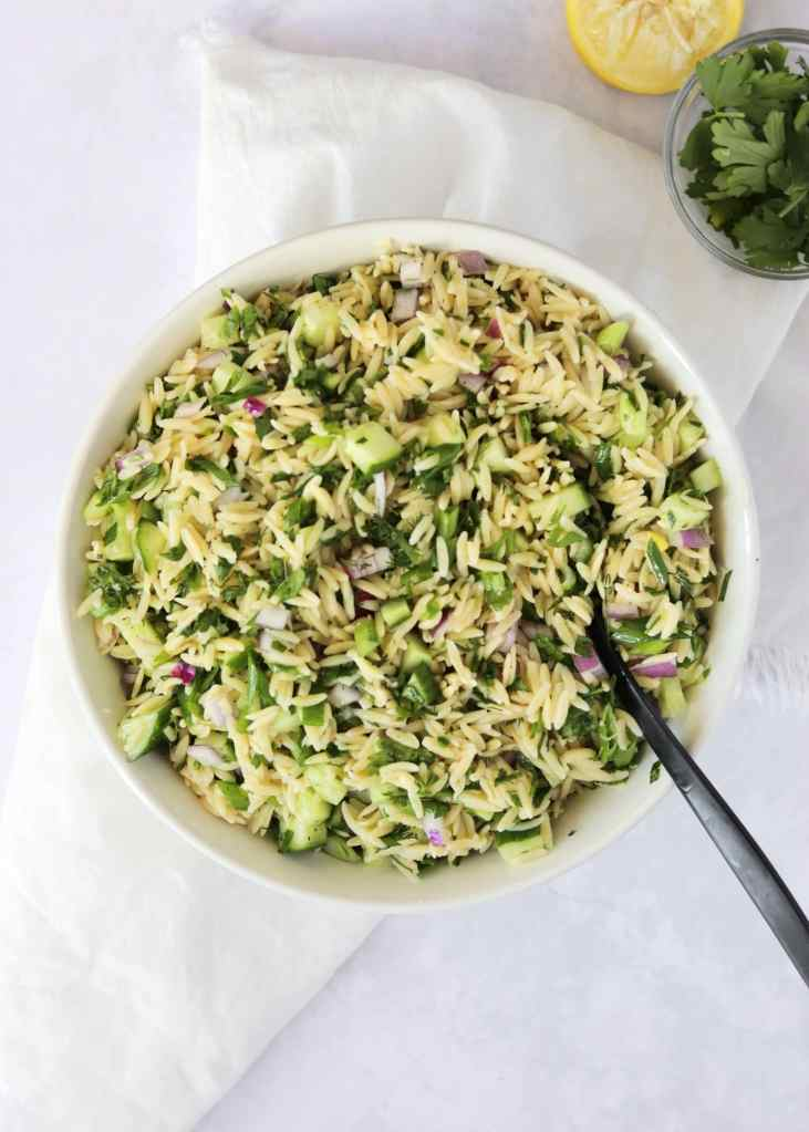 Herbed lemon orzo salad mixed together in large bowl with serving spoon