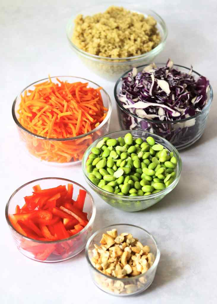 Quinoa, shredded cabbage, shredded carrots, edamame, bell pepper, and cashews in glass bowls