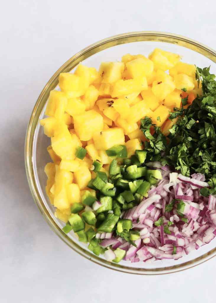 Pineapple salsa ingredients in glass bowl