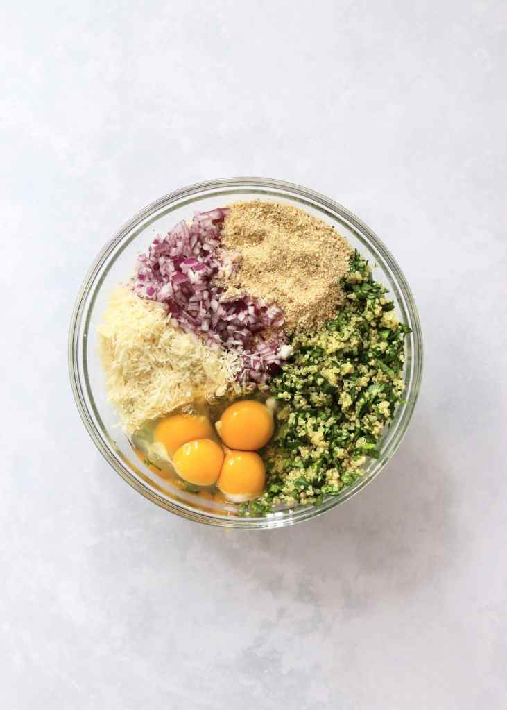 Quinoa, spinach, breadcrumbs, cheese, red onion, and eggs in a bowl.