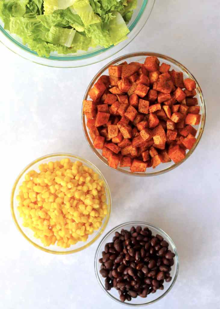Lettuce, roasted sweet potatoes, corn, and black beans in bowls