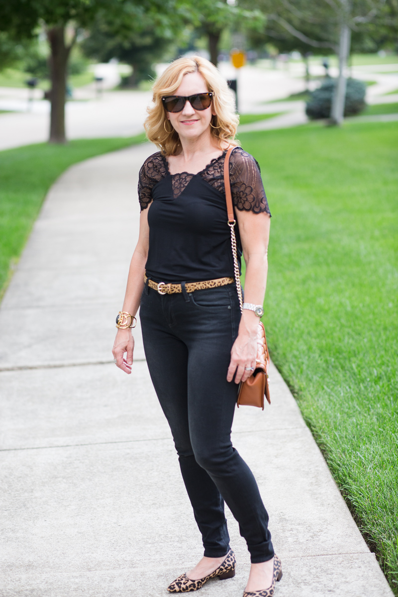 Black jeans with a black bodysuit and leopard accessories