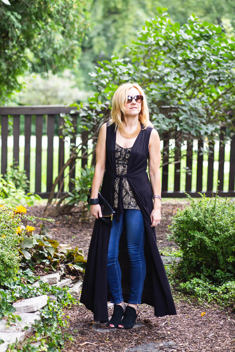 Long black vest and printed camisole top with skinny jeans, and heels.