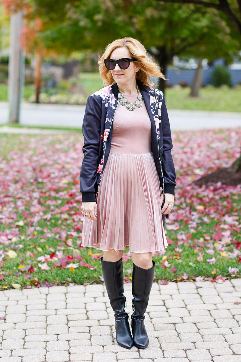 Pink pleated velvet dress paired with a black floral bomber for a chic Thanksgiving outfit.