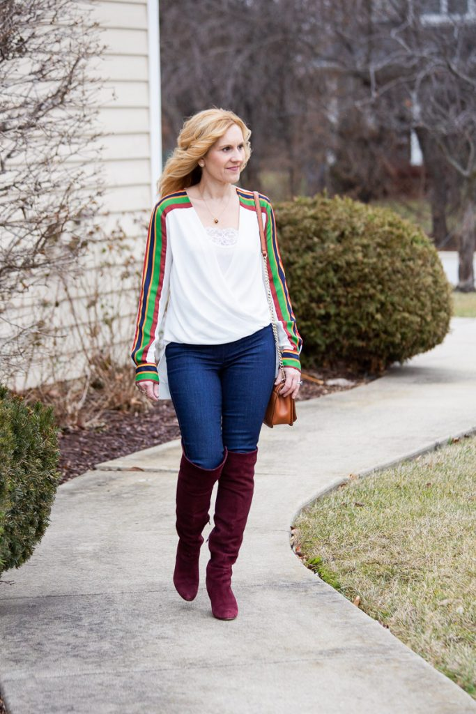 Sporty athleisure look featuring a striped high-low top with skinny jeans and otk boots.
