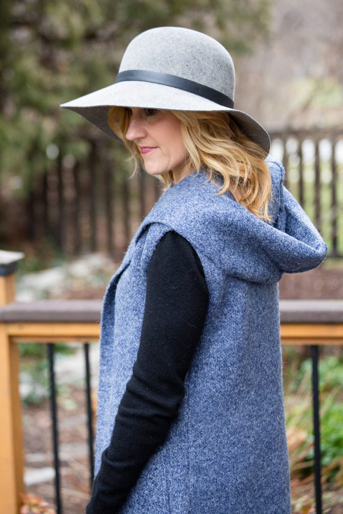 Blue hooded vest over a black cashmere sweater with a grey winter hat.