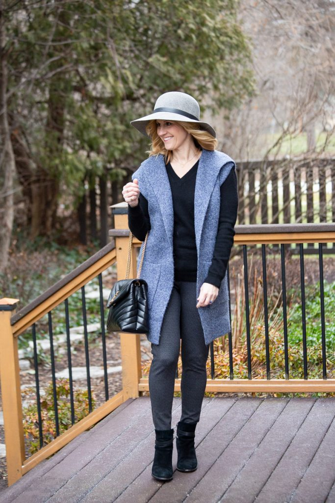 Cozy layered look featuring a blue long hooded vest, black cashmere sweater, and printed leggings.