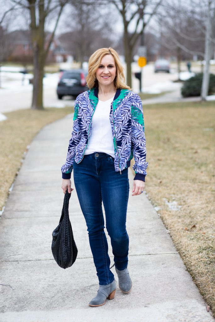 Wearing a blue printed bomber with dark jeans and suede booties.