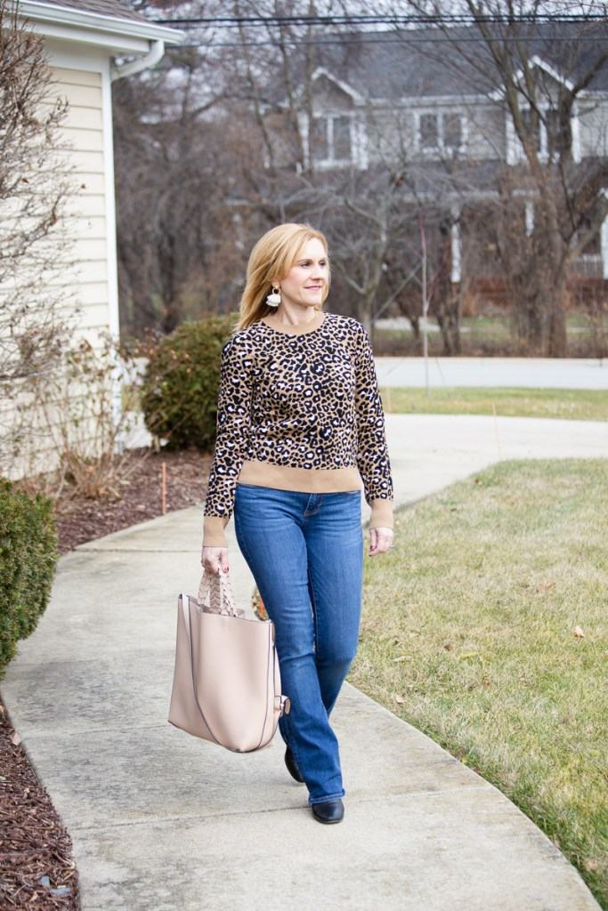 Styling a leopard print sweater with bootcut jeans and a pale pink tote.