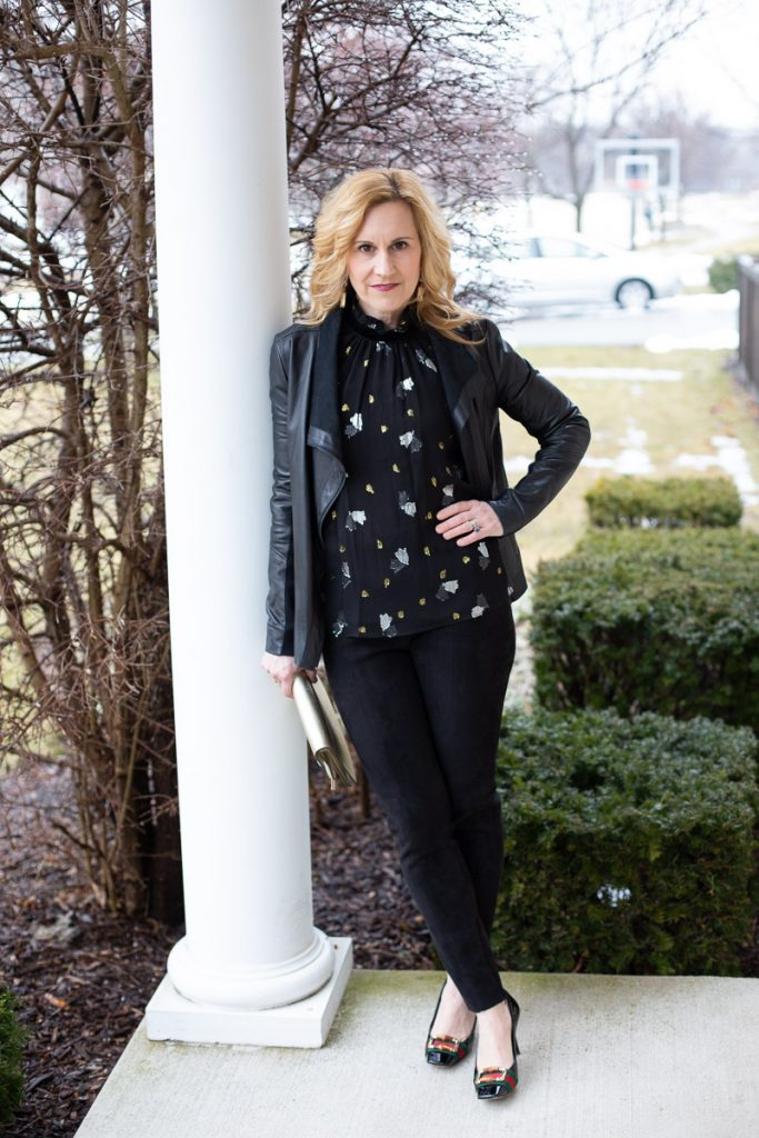 An all black outfit featuring a leather jacket, sleeveless blouse, and faux suede leggings.