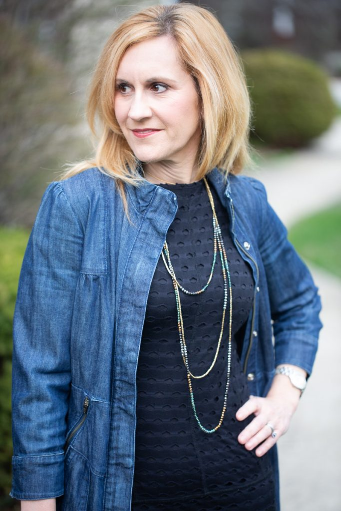 A long denim jacket paired with a little black dress.