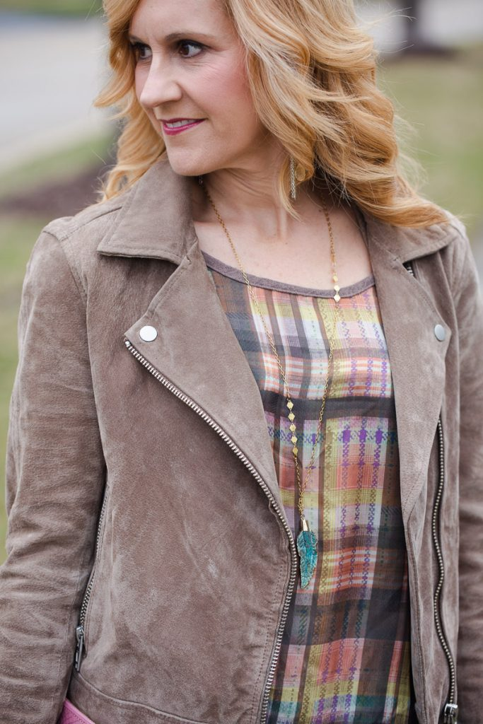 Styling a beige suede moto jacket with a plaid blouse and feather pendant necklace.