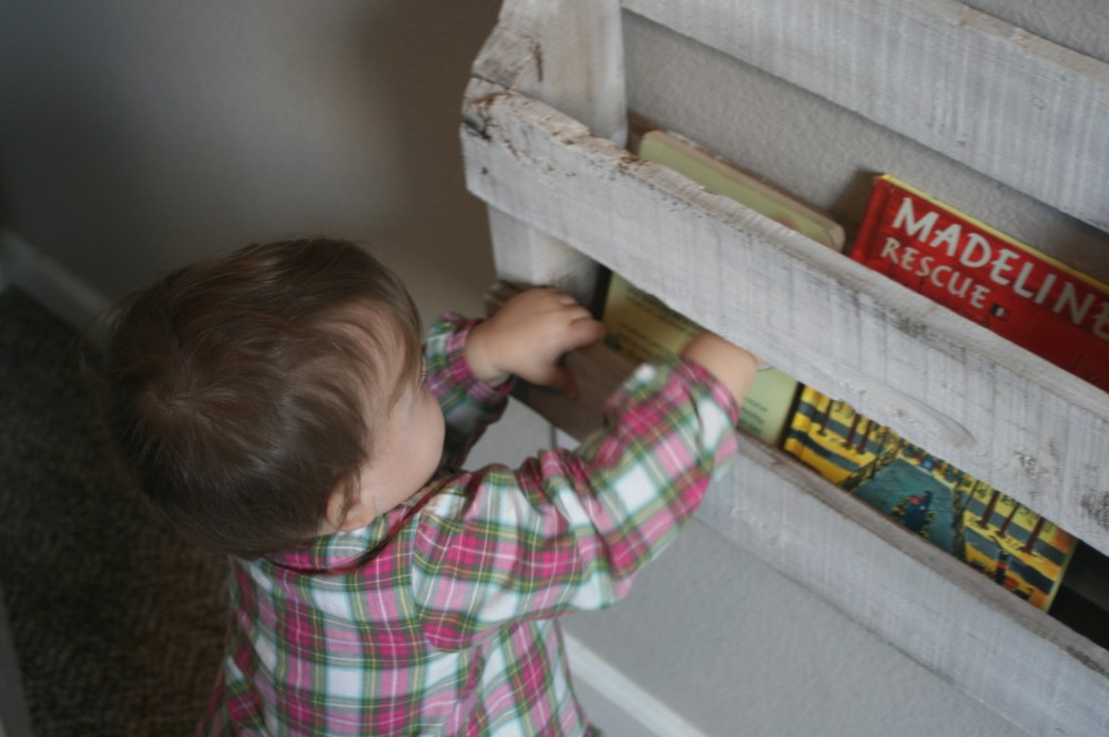 Photo of toddler reaching for book through pallet bookshelves