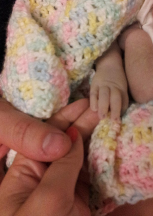 close up of parents' fingers holding their daughters hand, wrapped in a baby blanket